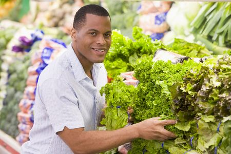 grocery store series: Man shopping for lettuce at a grocery store