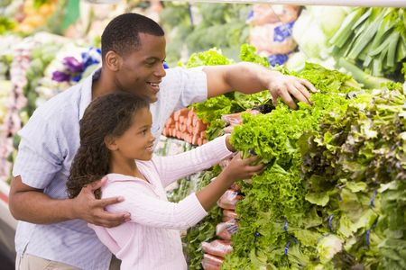 fresh produce: Father and daughter shopping for lettuce at a grocery store Stock Photo
