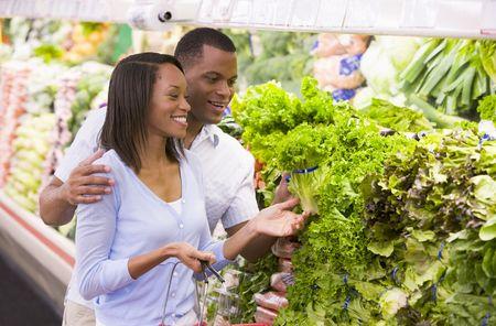 negocios comida: Pareja joven de compras para la lechuga en una tienda de comestibles