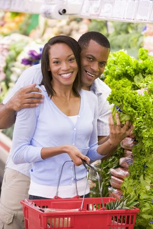 help section: Young couple shopping for lettuce at a grocery store Stock Photo