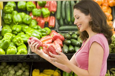 Woman shopping for bell peppers at a grocery store photo