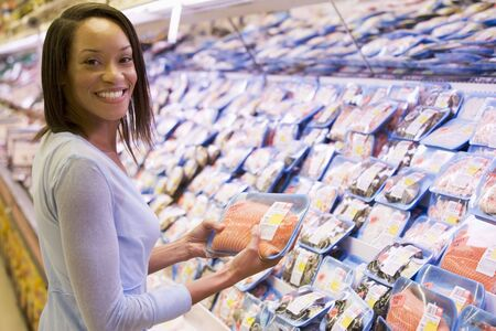 Woman shopping for fish and seafood at a grocery store photo