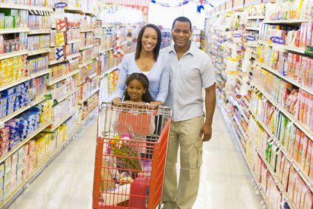 tiendas de comida: Madre y padre con hija de compras en el supermercado.