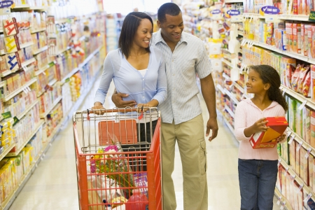 Mother and father with young daughter shopping at the grocery store.