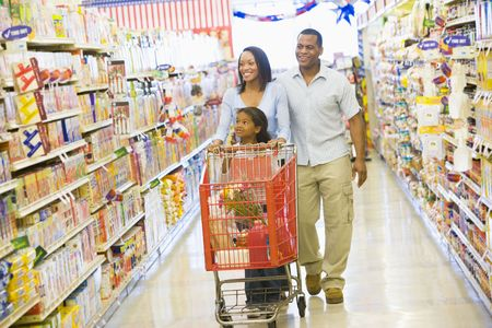 supermarket series: Mother and father with young daughter shopping at the grocery store.