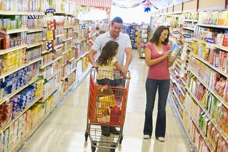 stores: Vader en moeder met jonge dochter winkelen bij de supermarkt. Stockfoto