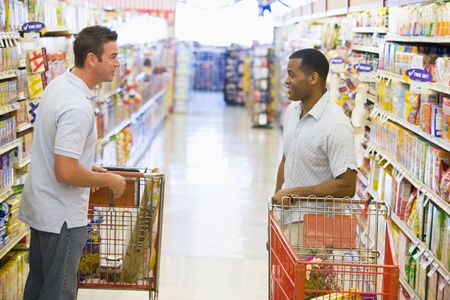 two people talking: Two men talking to each other at a grocery store