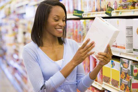 tiendas de comida: Mujer de compras en una tienda de comestibles  Foto de archivo