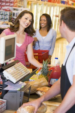 Women paying for purchases at a grocery store photo