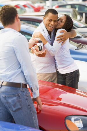 new car lot: Young couple shopping for a new car Stock Photo