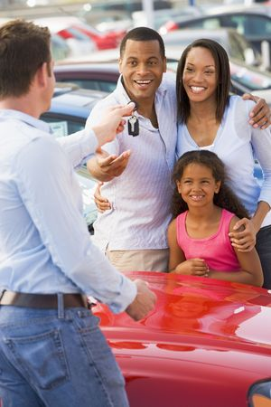 new motor car: Mother and father with young daughter shopping for a new car