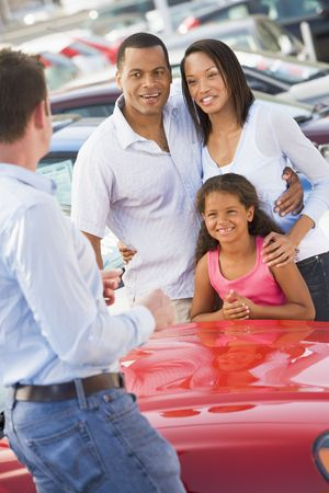 new car lots: Mother and father with young daughter shopping for a new car