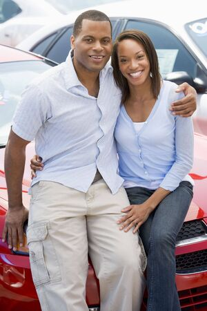 looking towards camera: Young couple shopping for a new car Stock Photo