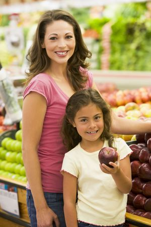 Woman and daughter shopping for apples at a grocery store photo