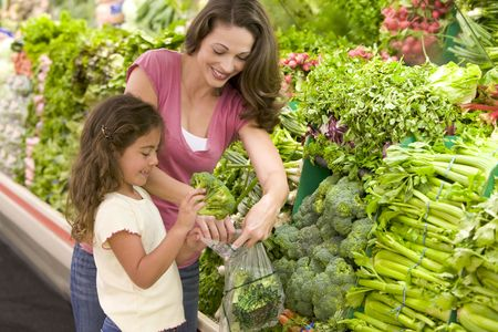 selections: Mother and daughter shopping for broccoli at a grocery store