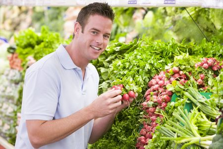 Man shopping for beets at a grocery store