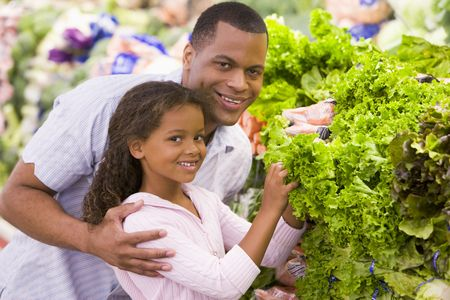 help section: Father and daughter shopping for lettuce at a grocery store Stock Photo