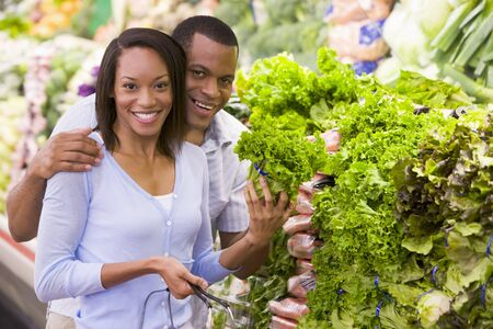 Young couple shopping for lettuce at a grocery store photo