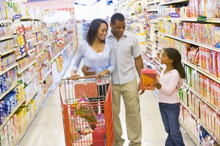 shopping carts: Mother and father with young daughter shopping at the grocery store.
