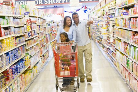 Mother and father with young daughter shopping at the grocery store. photo