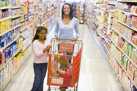 Mother and young daughter shopping at a grocery store photo