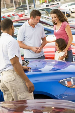 new motor car: Mother Father and young daughter shopping for a new car