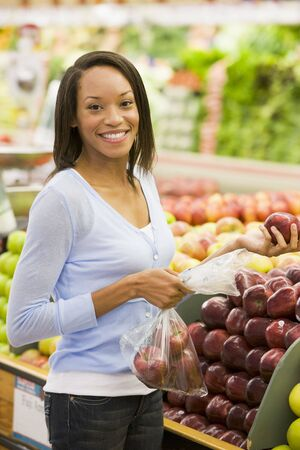 produce sections: Woman shopping for apples at a grocery store