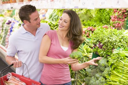 Young couple shopping for broccoli at a grocery store Stock Photo - 28198554