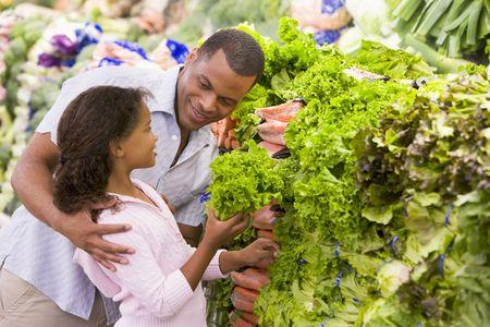 tiendas de comida: Padre e hija de compras para la lechuga en una tienda de comestibles