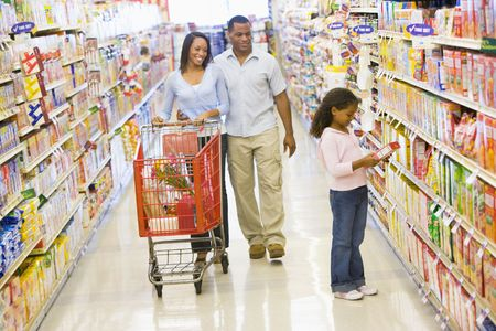 checking ingredients: Mother and father with young daughter shopping at a grocery store. Stock Photo