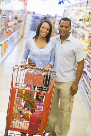looking towards camera: Young couple shopping at a grocery store