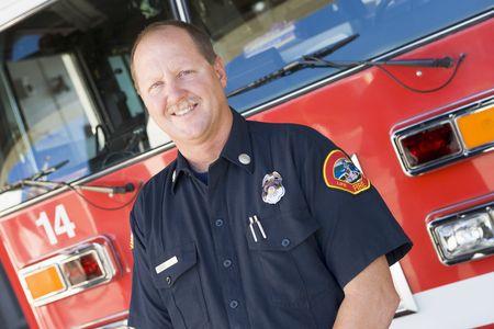 motor ardiendo: Los bomberos de pie delante del cami�n de bomberos  Foto de archivo