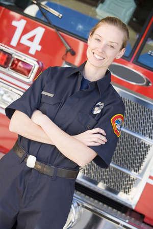 motor ardiendo: Firewoman de pie delante del cami�n de bomberos