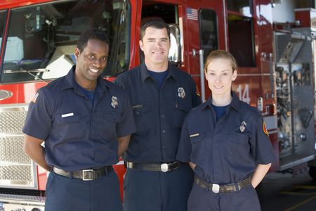Three firefighters standing in front of fire engine photo
