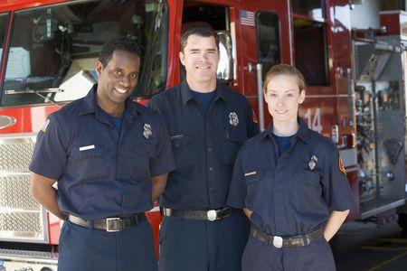motor ardiendo: Tres bomberos de pie delante del cami�n de bomberos  Foto de archivo