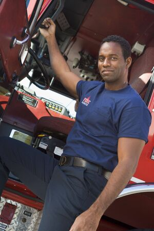leaning on the truck: Fireman leaning in door of fire engine