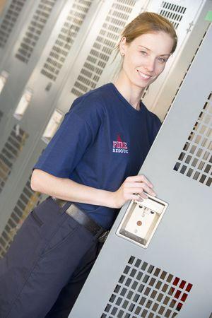 locker room: Firewoman holding her locker door open in fire station locker room (depth of field)
