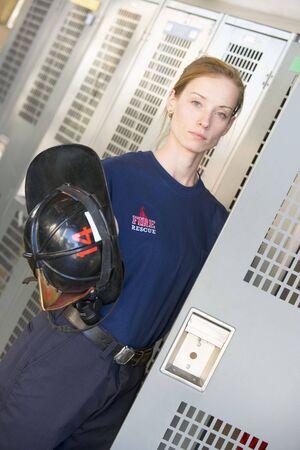 offset angle: Firewoman getting her helmet out of her locker in fire station locker room (depth of field)