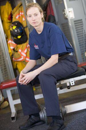 estacion de bomberos: Firewoman sentado en el banco en estaci�n de bomberos vestuario