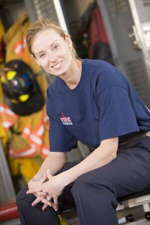 offset angles: Firewoman sitting on bench in fire station locker room Stock Photo