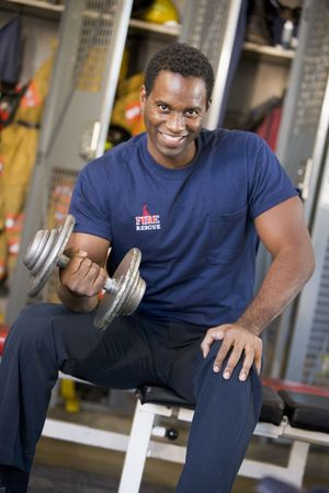 Fireman lifting dumbbell on bench in fire station locker room photo