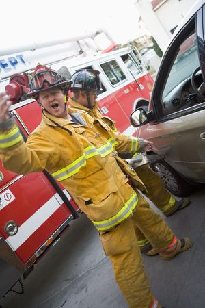 motioning: Fireman motioning for backup with another fireman using the jaws of life on a car door (blur)