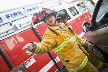 fireman helmet: Fireman pointing at something with another fireman using the jaws of life on a car door