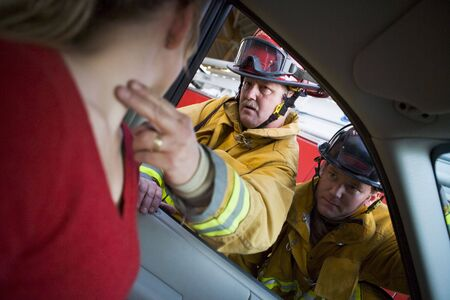 motorcars: Fireman taking womans pulse while another fireman watches (selective focus)
