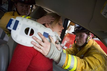 Two firemen helping woman with neck brace photo
