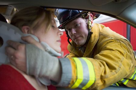 Fireman helping woman with neck brace (selective focus)