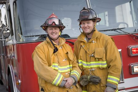 Two firemen standing in front of fire engine photo