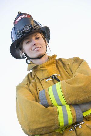 Firewoman standing outdoors wearing helmet photo