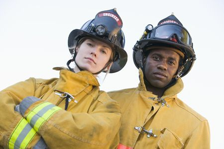 frontal views: Two firefighters standing outdoors wearing helmets