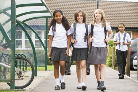 tween boy: Three students leaving school with other students in background